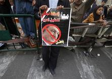 <p>Демонстрант держит плакат с перечеркнутым портретом президента Египта Хосни Мубарака возле здания парламента в Каире 10 февраля 2011 года. Премьер-министр Египта Ахмед Шафик сообщил в четверг британской телерадиовещательной корпорации BBC, что президент Хосни Мубарак может уйти в отставку, а ситуация в стране в скором времени прояснится. REUTERS/Suhaib Salem</p>