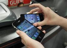 <p>Покупатель выбирает iPhone в магазине в Бока-Ратоне (Флорида), 10 февраля 2010 года. Apple Inc работает над созданием меньшей по размерам и более дешевой версии популярного смартфона iPhone, сообщает Bloomberg со ссылкой на источники. REUTERS/Joe Skipper</p>