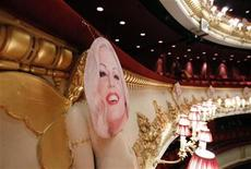 <p>A picture of Anna Nicole Smith hangs over one of the cherubs which decorate the balconies at the Royal Opera House, on the opening night of the opera based on her life, in central London, February 17, 2011. The genteel world of opera collides with that of lurid headlines, strip clubs and Playboy on Thursday when a new work based on the life of the late Smith has its premiere at London's Royal Opera House. REUTERS/Andrew Winning</p>