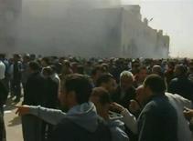 <p>Демонстранты перед окутанным дымом административным зданием в Бенгази 20 февраля 2011 года. Второй по величине город Ливии Бенгази лишился возможности принимать и отправлять пассажирские самолеты после того, как взлетно-посадочные полосы были уничтожены в ходе народных волнений, охвативших страну, сообщил министр иностранных дел Египта Ахмед Абул Гейт. REUTERS/Youtube via Reuters TV</p>