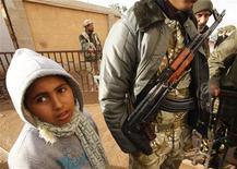 <p>Мальчик стоит рядом с солдатом в Бенгази, 24 февраля 2011 года. Лояльные лидеру Ливии Муаммару Каддафи войска атаковали находящиеся под контролем протестующих города близ столицы страны Триполи, однако не смогли выбить оттуда оппозицию. REUTERS/Suhaib Salem</p>