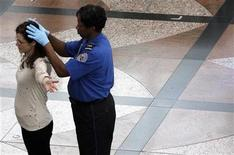 <p>A Transportation Security Agency (TSA) worker runs her hands over the head of a traveler during a patdown search at Denver International Airport, the day before Thanksgiving November 24, 2010. REUTERS/Rick Wilking</p>
