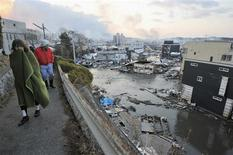 <p>Houses swept by a tsunami are seen as residents walk in Kesen Numa, Miyagi prefecture March 12, 2011. REUTERS/Kyodo</p>