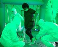 <p>Медицинский персонал проверяет женщину на возможное получение облучения в городе Хитати (Япония), 16 марта 2011 года. Руководство поврежденной землетрясением атомной станции в Японии ненадолго эвакуировало персонал с АЭС из-за увеличения уровня радиации, сообщило информагентство Kyodo. REUTERS/Asahi Shimbun</p>