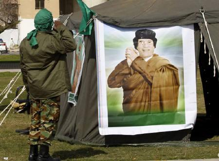 A security personnel salutes to a picture of leader Muammar Gaddafi near a checkpoint in Tripoli February 28, 2011. Gaddafi's army fought in vain to capture rebel-held Misrata on Friday and shelled the city into the evening, ignoring a ceasefire Libya declared, a resident in the embattled city said. REUTERS/Ahmed Jadallah
