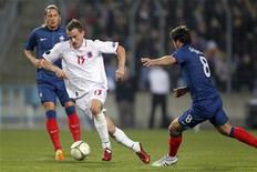 <p>Aurelien Joachim (centro), do Luxemburgo, em posse da bola, dribla Yoann Gourcuff (direita) e Philippe Mexes (esquerda) durante partida da Eurocopa de 2012 em Luxemburgo. 25/03/2011 REUTERS/Thierry Roge</p>