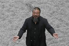 """<p>Chinese artist Ai Weiwei throws porcelain sunflower seeds into the air as he poses with his installation """"Sunflower Seeds"""", in the Turbine Hall at the Tate Modern gallery, in London in this October 11, 2010 file photo. REUTERS/Stefan Wermuth/Files</p>"""