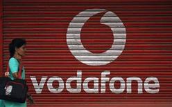 <p>Foto de archivo de una mujer pasando frente a una reja con el logo de la operadora telefónica Vodafone en Mumbai, mayo 20 2010. Las acciones de Vodafone subían un 2 por ciento el lunes, porque inversores y analistas consideraban que Vivendi había pagado un sólido precio para asegurarse el control completo de SFR, el segundo mayor operador de telefonía celular de Francia. REUTERS/Arko Datta</p>
