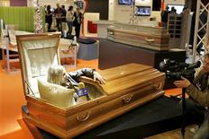 "<p>A television journalist speaks to the camera as she tries out a coffin, which is at the disposition of visitors to ""test-drive"" during media day at the ""Salon de la Mort"" (Funerary Show) in Paris April 7, 2011. Some 100 companies take part in the three-day event which presents services and funerary articles such as coffins, grave stones and urns. REUTERS/Charles Platiau</p>"