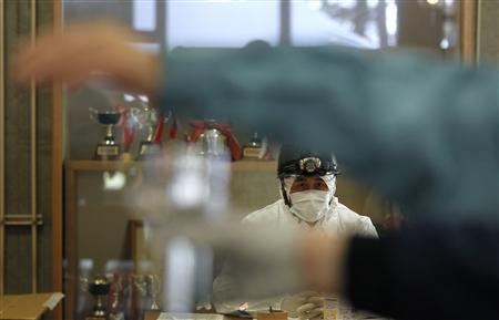 A member of Japan's Self-Defense Force, in a protective suit, watches as an evacuee is tested for radiation in Koriyama, Fukushima Prefecture, northern Japan, April 12, 2011. REUTERS/Kim Kyung-Hoon
