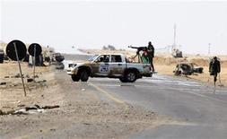 <p>A rebel fighter with an amputated leg (R) moves into a new position along the front line at the western entrance of Ajdabiyah April 14, 2011. REUTERS/Amr Abdallah Dalsh</p>