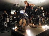 <p>A fitness instructor leads a SoulCycle class at their Union Square location in New York, April 13, 2011. Indoor cyclists routinely sweat a real river pedaling down an imaginary road, but SoulCycle classes add upper body work, and a touch of the spiritual, to their metaphorical journey. REUTERS/Shannon Stapleton</p>