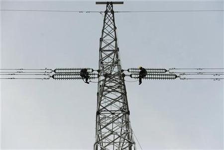 Workers install a new electricity pylon in Chuzhou, Anhui province January 2, 2011. REUTERS/China Daily