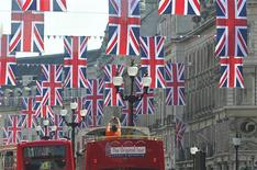 <p>A tourist photographs Union flags hung along Regent Street in celebration of the forthcoming royal wedding, in London, April 19, 2011. REUTERS/Toby Melville</p>