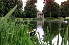 <p>The temple commemorating Diana, Princess of Wales, is reflected in the lake of her family home at Althorp, near Northampton on June 28, 2001. REUTERS/Ferran Paredes</p>