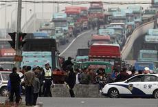 <p>Полицейский и водители грузовиков в районе стоянки грузовиков-контейнеровозов возле порта в Шанхае 21 апреля 2011 года. Водители грузовиков продолжили в пятницу забастовку в районе главной гавани Шанхая в окружении полицейских. REUTERS/Carlos Barria</p>