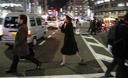 <p>A woman wearing a helmet walks through traffic chaos as people are forced to walk home between grid locked vehicles in central Tokyo after an earthquake off the coast of northern Japan March 11, 2011. REUTERS/Toru Hanai</p>