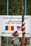 <p>Солдат распутывает флаг на американской военной базе под Бухарестом, 29 августа 2007 года. Румынские власти утвердили выбранное ранее место для строительства американской ракетной базы, которая станет одним из элементов европейского противоракетного щита, заявил президент Румынии Траян Бэсеску. REUTERS/Mihai Barbu</p>