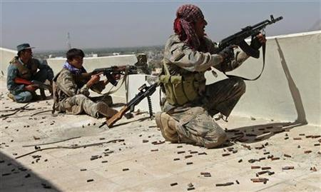 Afghan border police fire at the Taliban forces from a rooftop during clashes in Kandahar city May 8, 2011. REUTERS/Ahmad Nadeem