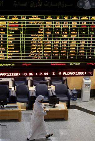 A trader walks under a screen showing stock information at the Emirates Securities Market in Abu Dhabi December 12, 2010. REUTERS/Fadi Al-Assaad