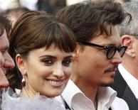 """<p>Cast members Penelope Cruz and Johnny Depp pose as they arrive on the red carpet for the screening of their film """"Pirates Of The Caribbean: On Stranger Tides"""" at the 64th Cannes Film Festival, May 14, 2011. REUTERS/Yves Herman</p>"""