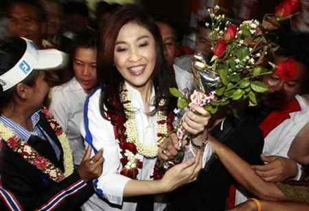 Yingluck Shinawatra, sister of toppled premier Thaksin Shinawatra and the prime ministerial candidate for the country's biggest opposition Puea Thai Party, gestures to her supporters during an election campaign in Udon Thani province, east of Bangkok May 25, 2011. REUTERS/Sukree Sukplang