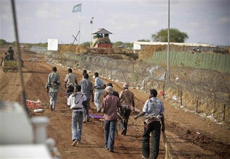 Armed men walk past a U.N. peacekeeping mission (UNMIS) camp in Abyei town May 24, 2011. REUTERS/Stuart Price/UNMIS