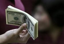 <p>An employee working as a money changer prepares U.S. dollar currency for a customer in Jakarta October 28, 2008. REUTERS/Enny Nuraheni</p>