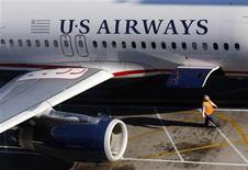 <p>A ground crew worker walks past a U.S. Airways aircraft outside terminal 4 at Phoenix International Airport in Phoenix, April 8, 2010. REUTERS/Joshua Lott</p>