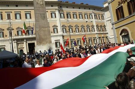 Protesters wave a big Italian flag during a protest against Italy's Prime Minister Silvio Berlusconi in front of the Italian Parliament in downtown Rome April 5, 2011. REUTERS/Tony Gentile