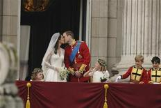 <p>Britain's Prince William and his wife Catherine, Duchess of Cambridge kiss on the balcony at Buckingham Palace, watched by bridemaids Grace van Cutsem (L) and Margarita Armstrong-Jones and pageboy Tom Pettifer, after their wedding in Westminster Abbey, in central London April 29, 2011. REUTERS/Dylan Martinez</p>