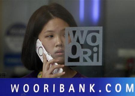 Customer uses her mobile phone at a branch office of Woori Bank in Seoul July 20, 2010.REUTERS/Truth Leem