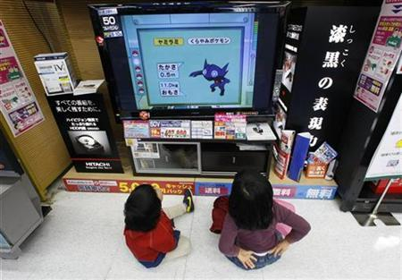Children sit on the floor watching television at an electronics shop in Tokyo February 2, 2009. REUTERS/Yuriko Nakao