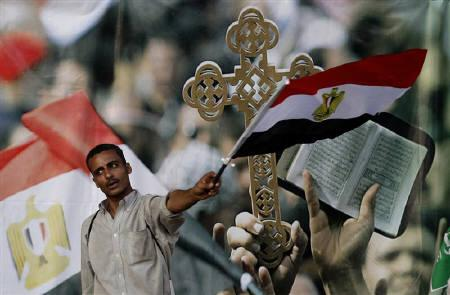 A protester waves an Egyptian flag in front of a picture of a Cross and a Koran, symbols of the country's unity, at Tahrir square in Cairo July 11, 2011. REUTERS/Mohamed Abd El-Ghany
