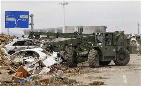 A construction vehicle from the U.S. Marines clears debris at Sendai airport which was damaged by the March 11 earthquake and tsunami, in Miyagi Prefecture March 25, 2011. REUTERS/Kim Kyung-Hoon