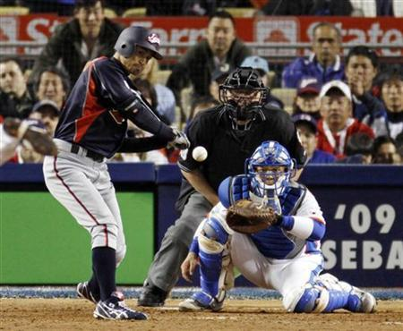 Team Japan's Ichiro Suzuki (L) hits a two RBI double in front of Team Korea catcher Park Kyung-Oan (R) during the tenth inning of play in the World Baseball Classic championship game in Los Angeles, California March 23, 2009. REUTERS/Fred Greaves