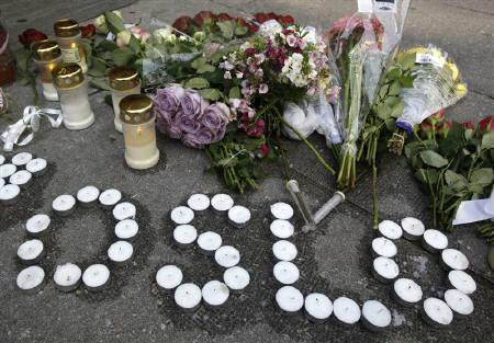 Candles and flowers are arranged on the ground near the blast site to mourn the victims of a rampage on an island and in the capital Oslo July 23, 2011. REUTERS/Wolfgang Rattay