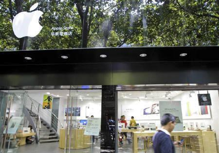 A pedestrian uses his cell phone as he walks past a fake Apple store in Kunming, Yunnan province July 21, 2011. Chinese officials in Kunming ordered two fake Apple shops to close, an apparent reaction to a storm of media attention about an unauthorised and elaborate hoax store in the southwestern city. REUTERS/China Daily