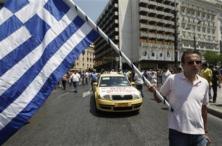 A taxi driver holds a Greek flag as he protests during a rally in Athens, July 19, 2011. REUTERS/John Kolesidis