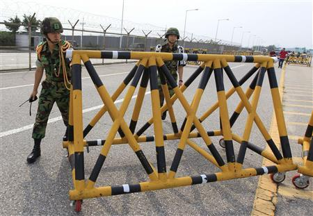 Army soldiers remove a barricade for trucks carrying sacks of flour to North Korea at a checkpoint in front of the Unification Bridge near the demilitarized zone separating the two Koreas in Paju, about 55 km (34 miles) north of Seoul, July 26, 2011. REUTERS/Jo Yong-Hak