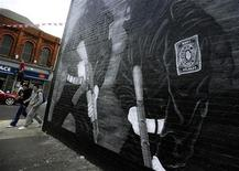 <p>Locals pass a mural showing loyalist Ulster Volunteer Force (UVF) gunmen on a wall in a predominantly protestant area of east Belfast June 23, 2011. REUTERS/Dylan Martinez</p>
