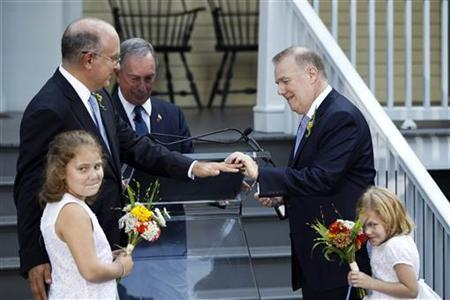 Jonathan Mintz (2nd L), New York City's consumer affairs commissioner, has a wedding ring placed on his finger by John Feinblatt (R), a chief adviser to the mayor, as they stand with daughters Maeve (L) and Georgia during a marriage ceremony presided by New York City Mayor Michael Bloomberg (C) at Gracie Mansion in New York July 24, 2011. REUTERS/Lucas Jackson