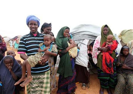A displaced family from Somalia stand in front of their makeshift shelter in south Mogadishu in Hodan district August 1, 2011. REUTERS/Feisal Omar
