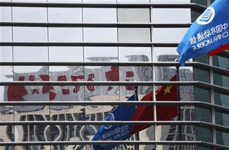 A China Mobile company flag and the Chinese national flag are reflected in the windows of the China Mobile building in central Beijing September 8, 2010. REUTERS/Petar Kujundzic