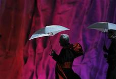 <p>Priests shelter themselves from the rain underneath umbrellas as they leave after a prayer vigil at the Cuatro Vientos aerodrome as part of World Youth Day festivities in Madrid, August 20, 2011. REUTERS/Susana Vera</p>