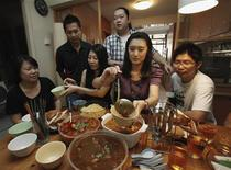 "<p>Organizers of ""Cook A Pot of Curry"" Facebook event Stanley Wong (2nd L), Florence Leow (3rd L) and Gabriel Yeap (C) eat curry with friends including Liang Meizi (2nd R) from China during a photocall at Leow's home in Singapore August 21, 2011. REUTERS/Edgar Su</p>"