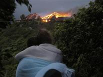 <p>Two people watch as a fire sweeps through Richard Branson's Caribbean holiday retreat in this photograph taken and released August 22, 2011 by Virgin Management Ltd. The blaze in the Great House on Necker Island, was caused by a lightning strike and the building was completely destroyed, the billionaire said on Monday. British Oscar-winning actress Kate Winslet was among the guests who escaped unhurt from the fire along her boyfriend, and family, and Branson's mother Eve. REUTERS/Courtesy Virgin Management Ltd./Handout</p>