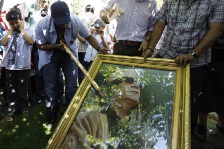 Demonstrators smash a poster of Libyan leader Muammar Gaddafi during a protest against Gaddafi outside of the Libyan embassy in Ankara August 22, 2011. REUTERS/Umit Bektas