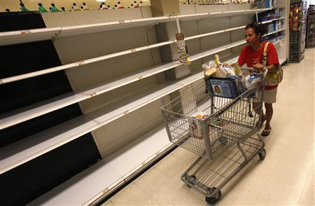 A shopper passes empty shelves while looking for bottled water at a supermarket in Long Beach on Long Island, New York, August 26, 2011. REUTERS/Mike Segar