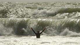 <p>A man wades into the waves of a storm surge created by the passing of Hurricane Irene at Lawrencetown beach, Nova Scotia, August 29, 2011. REUTERS/Paul Darrow</p>